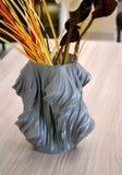 Ein grauer Vase, der auf einem Drucker 3d gedruckt wird, steht auf einer Tabelle im Innenraum Stockfoto