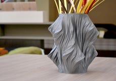 Ein grauer Vase, der auf einem Drucker 3d gedruckt wird, steht auf einer Tabelle in der Innennahaufnahme Stockfotografie