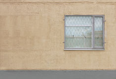 ein graues Fenster mit einem Sicherheitsschutz auf dem ersten Stockwerk des beige Hintergrundes des modernen Gebäudes vergipste W Stockfotografie