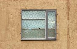 ein graues Fenster mit einem Sicherheitsschutz auf dem ersten Stockwerk des beige Hintergrundes des modernen Gebäudes vergipste W Stockbild