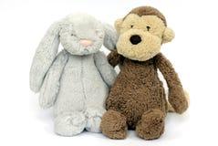 Ein graues flaumiges Kaninchenspielzeug und ein weicher brauner Affe spielen Stockfotos