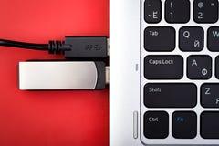 Ein greller Antrieb und ein Draht von einem externen Festplattenlaufwerk schlossen an einen Laptop auf einem roten Hintergrund an Lizenzfreies Stockfoto