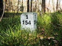 Ein Grenzpfeiler mit einem Zeichen herein der Wald stockbild