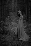 Ein grimmiger Minireaper, der eine Sense anhält, steht auf einem Kalendertag, der glückliches Halloween sagt Eine Hexe in einer s Lizenzfreies Stockbild