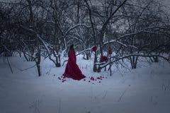 Ein grimmiger Minireaper, der eine Sense anhält, steht auf einem Kalendertag, der glückliches Halloween sagt Eine Hexe in einer r Stockfoto
