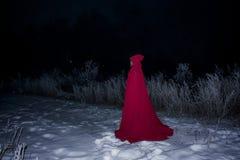 Ein grimmiger Minireaper, der eine Sense anhält, steht auf einem Kalendertag, der glückliches Halloween sagt Hexe im Rot gegen Stockfotos
