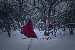 Ein grimmiger Minireaper, der eine Sense anhält, steht auf einem Kalendertag, der glückliches Halloween sagt Hexe im Rot gegen Lizenzfreies Stockbild