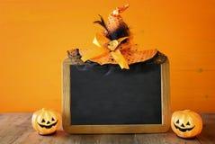 Ein grimmiger Minireaper, der eine Sense anhält, steht auf einem Kalendertag, der glückliches Halloween sagt Kürbise nahe bei lee Lizenzfreie Stockbilder