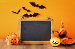 Ein grimmiger Minireaper, der eine Sense anhält, steht auf einem Kalendertag, der glückliches Halloween sagt Kürbise nahe bei lee Lizenzfreie Stockfotografie