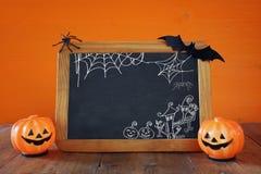 Ein grimmiger Minireaper, der eine Sense anhält, steht auf einem Kalendertag, der glückliches Halloween sagt Nette Kürbise nahe b Stockfoto