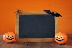 Ein grimmiger Minireaper, der eine Sense anhält, steht auf einem Kalendertag, der glückliches Halloween sagt Nette Kürbise nahe b Stockbild