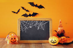 Ein grimmiger Minireaper, der eine Sense anhält, steht auf einem Kalendertag, der glückliches Halloween sagt Nette Kürbise nahe b Stockfotos