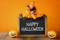 Ein grimmiger Minireaper, der eine Sense anhält, steht auf einem Kalendertag, der glückliches Halloween sagt Nette Kürbise nahe b Stockbilder