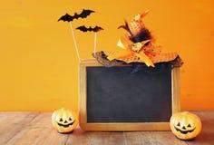 Ein grimmiger Minireaper, der eine Sense anhält, steht auf einem Kalendertag, der glückliches Halloween sagt Netter Kürbis auf Ho Lizenzfreie Stockfotografie