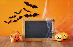 Ein grimmiger Minireaper, der eine Sense anhält, steht auf einem Kalendertag, der glückliches Halloween sagt Netter Kürbis auf Ho Stockfotos