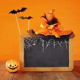 Ein grimmiger Minireaper, der eine Sense anhält, steht auf einem Kalendertag, der glückliches Halloween sagt Netter Kürbis auf Ho Stockbild