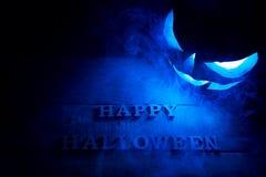 Ein grimmiger Minireaper, der eine Sense anhält, steht auf einem Kalendertag, der glückliches Halloween sagt Hintergrund des myst Lizenzfreie Stockfotografie