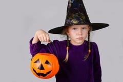 Ein grimmiger Minireaper, der eine Sense anhält, steht auf einem Kalendertag, der glückliches Halloween sagt Schönes Kindermädche Lizenzfreie Stockfotografie