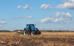 Ein großer blauer Traktor, Feld gegen den schönen Himmel pflügend Lizenzfreie Stockfotografie