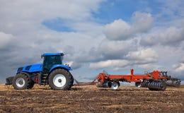 Ein großer blauer Traktor, Feld gegen den schönen Himmel pflügend Stockfotografie
