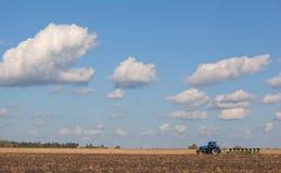 Ein großer blauer Traktor, Feld gegen den schönen Himmel pflügend Stockbild