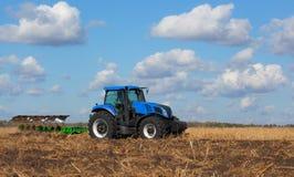 Ein großer blauer Traktor, Feld gegen den schönen Himmel pflügend Lizenzfreies Stockfoto