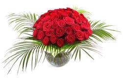 Ein großer Blumenstrauß von roten Rosen in einem transparenten Glasvase. Das lokalisierte Bild auf einem weißen Hintergrund. Lizenzfreie Stockfotos