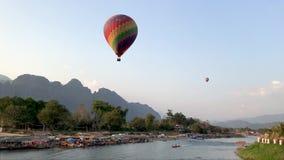 Ein großer bunter Ballon fliegt über den Fluss in Laos