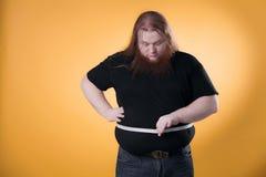 Ein großer dicker Mann misst seine großen Größen mit einem Band lizenzfreie stockfotos