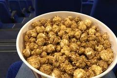 Ein großer Eimer köstliches Karamellpopcorn auf dem Schoss eines Mannes, der auf den Film wartet, um am Kino zu beginnen lizenzfreies stockbild