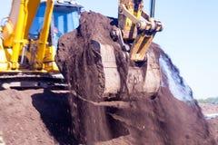 Ein großer Eisenbaggereimer sammelt und gießt Sandschutt und -steine in einem Steinbruch an der Baustelle von Straßenanlagen lizenzfreie stockfotografie
