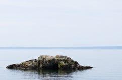 Ein großer Felsen im See Stockfotografie