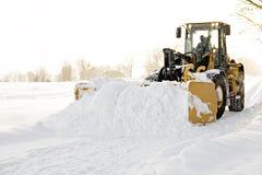 Ein großer gelber Schneepflug, der eine Straße säubert lizenzfreies stockbild