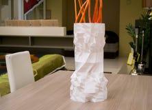 Ein großer hoher weißer Vase, der mit einem Drucker 3d gedruckt wird, steht auf einer Tabelle Stockfoto