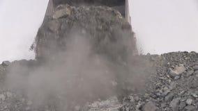 Ein großer Kipplaster gießt 50 Tonnen Erz in die Klippe stock footage