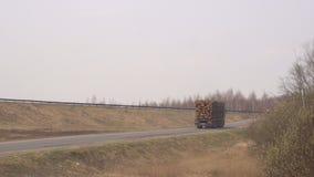Ein großer LKW-Lastwagen transportiert Bauholz, Holz anmeldet die Landstraße, Kopienraum stock footage