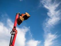 Ein großer roter Baubaggereimer über dem blauen Himmel bereit zum Abbauen Stockfotografie