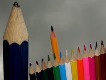 Ein großer schäbiger Bleistift, stehend neben einer kleinen Gruppe intelligentes Scharfes farbigen Bleistiften stockbilder