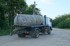 Ein großer schmutziger LKW mit einem Behälter und ein Schlauch für Straße cannonage heraus pumpen Lizenzfreie Stockfotografie