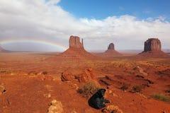 Ein großer schwarzer Hund unter einem Regenbogen Lizenzfreie Stockfotografie
