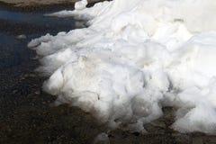 Ein großer Stapel des schmutzigen weißen Schnees liegt auf der Asphaltstraße Lizenzfreies Stockbild
