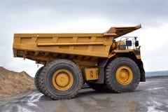 Ein großer Steinbruch-LKW der gelben Farbe wird von der Seite entfernt stockfotos