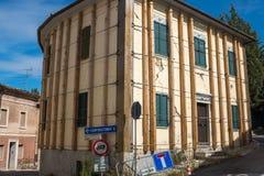 Ein großer Wohnblock in einem italienischen Dorf, dem durch ein Erdbeben beschädigt worden ist und durch Stahldrähte zu eingewick stockfotos