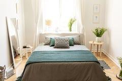 Ein großes Bett kleidete in den Erdfarben an, die mit Kissen Leinen sind und in einer Decke, die in einem eco freundlichen Schlaf stockfoto