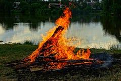 Ein großes Feuer auf dem Ufer des Sees an der Dämmerung Stockfoto