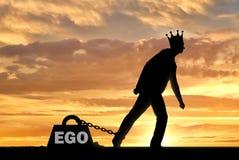 Ein großes Gewicht in Form eines Egos wird an den Fuß eines egoistischen und narzisstischen Mannes mit einer Krone auf seinem Kop lizenzfreie stockfotografie