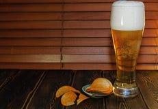 Ein großes Glas Bier und Kartoffelchips Lizenzfreie Stockfotos