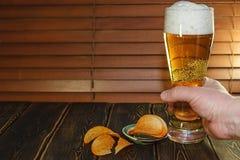 Ein großes Glas Bier und Kartoffelchips Stockbilder
