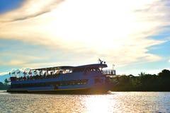 Ein großes Kreuzschiff-tragende Touristen überschreiten durch mein kleines Boot lizenzfreie stockbilder