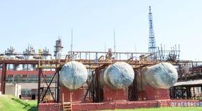 Ein großes metallisches Eisenrohrleitungsgestell mit Rohren und Drähten für Strom in einer petrochemischen chemischen Raffinerie  stockbild